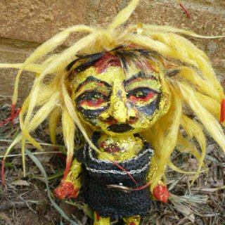 I repainted an old abandoned plastic doll using acrylic paints, glitter paints,paperclay for the nose,recycled jewelry,recycled fabric,and gloss medium for the hair to make dreads. I also papier mached her face and body before painting.