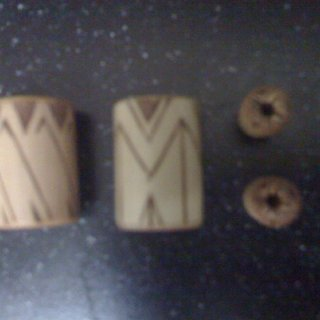 So I had these custom made and they are bamboo. The guy put burn patterns on the core of the ear plugs (0g) and on the outside of the dread beads. I told him to use his discretion, but I wanted the plugs to match and the beads to be different (they are about an inch long and have about 8mm holes inside them). Said I'd like a native type feel to them, but I trusted him as an artist to do better without much guidance. It paid off, I'm pleased! Picture came out a bit blurry but you get the idea.