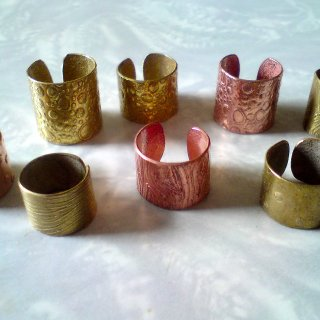 These are textured metal dread cuffs that I make. They're made from recycled copper and brass, and they don't cost much at all. contact me if you'd like some! a percentage of profit will go to this site (with love)