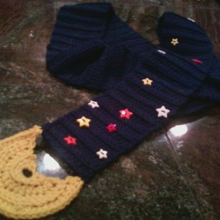 "One of my first projects. Narrow scarf with a spray of star buttons and crocheted ""moon"" at 1 end."