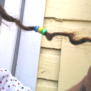 """This is one of the locs that formed out of a bit of loose hair. Since the frizzies are starting to grow out these tiny ones have been popping up like mad! I'm loving them, though! This one was the only one of the """"teeny locs"""" that would hold those little beads on it at the time and I really wanted a bit of color in there :-)"""