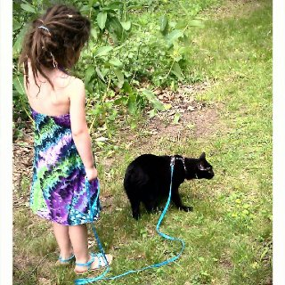 A 5 year old Gilly with 7 month old dreads taking our Manx cat, Bastian out for a walk in summer of 2012