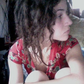 here, you can see my experimental side...also known as the side where three dreads fell off...which is why there are ringlets...they're just little babies! :) !