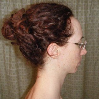 I can't replicate this updo now but it's a bun made with the middle stripe of hair from front to back and then the sides are twisted up and then draped over the top of the bun before a scrunchie is put over the main bun part. The pressure of the scrunchie seems to hold up the side twists well enough. It was very comfortable. Too bad I've not been able to do it again! lol.