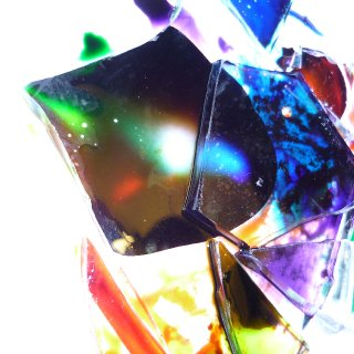 Shards of glass with water, oil, and food coloring on white plate