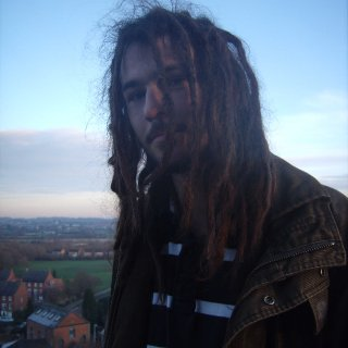 On top of a hill. Wind blowing. Frizzy dreadlocks.