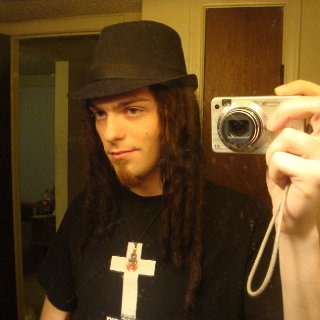 me in a fedora that im just now able to squeeze back into now that my locks are starting to lock and compress. btw thats a justice shirt, a great french electronica duo, not a christian shirt.