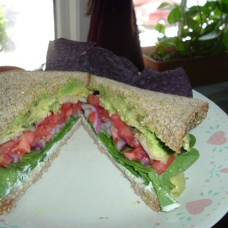 Avocado, hydroponic homegrown tomatoes,red onions, button mushrooms,baby spinach w/ vegenaise & agave mustard ( homemade ) on organic sprouted grains (sesame) bread-- w/ blue corn ( organic ) chips--All Organic---mmmmmm-- that's for lunch---Aloha