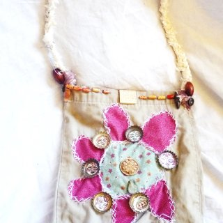 I created this purse by dyeing the fabric with coffee and tea and then handsewing it together. I used recycled fabrics,beads,and bottle cap buttons to create this piece.